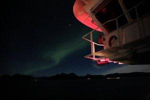 Brücke der MS Polarlys mit rotem Backbord-Positionslicht und Aurora Borealis